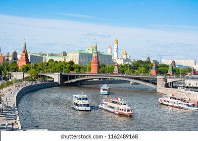 Moscow cityscape during midday over Moscow River with Bolshoy Kamenny Bridge and Moscow Kremlin in the distance.