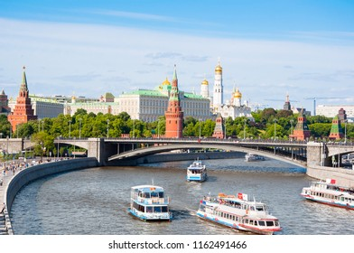 Moscow cityscape during midday over Moscow River with steel arch Bolshoy Kamenny Bridge spanning Moskva River at the western end of the Moscow Kremlin.