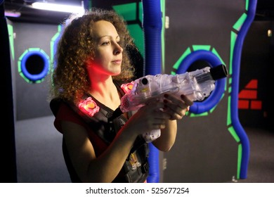 MOSCOW - DEC 13, 2014: Woman with curly hair (with model release) in a special vest with a laser-automat in laser tag at the shopping center Capitol Vernadsky