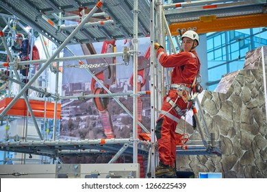 MOSCOW, DEC.11, 2018: Rescue worker in red uniform and helmet with climbing equipment are showing how to do rescue operation at height. Rescue training and climbing technique demonstration