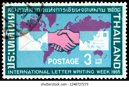 MOSCOW, December 1, 2018:  CIRCA 1965: Brown color postage stamp printed in Thailand with image of a handshake against a world map to commemorate International Letter Writing Week.