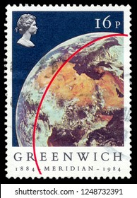 MOSCOW, December 1, 2018: A stamp printed in UK shows portrait of Elizabeth II and Earth (View from Apollo 11), inscriptions Greenwich Meridian, series ?entenery of Greenwich Meridian, circa 1984