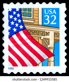 MOSCOW, December 1, 2018: stamp printed in United States shows American flag on the background of house and blue sky, circa 1995