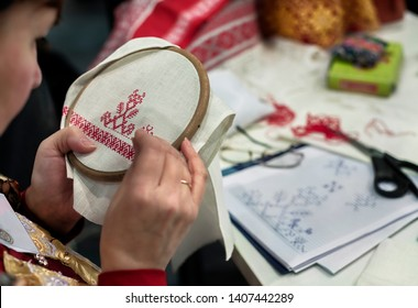 """Moscow. December 17, 2015. Annual exhibition """"Rook"""". The craftswoman embroiders a national Russian pattern with red thread on a white linen napkin"""
