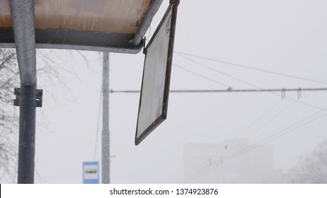 MOSCOW - DECEMBER 20, 2018: At the bus stop in the wind in winter swinging board with the timetable December 20, 2018 in Moscow, Russia