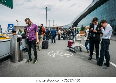 Moscow, Domodedovo, Russia - May 29, 2017: People smoke in the area for smokers or smoking area at the entrance to the Domodedovo International Airport