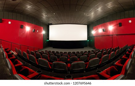 Moscow - Feb 14, 2012: Panoramic view of an empty cinema hall with a screen. Contemporary cinema auditorium design with red seats. Not full spherical panorama of the modern movie theater interior.