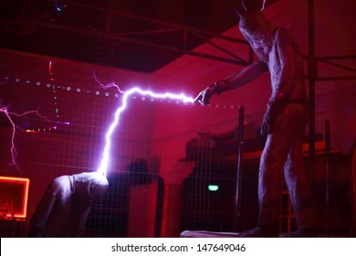MOSCOW - FEBRUARY 8: Man wins another man by lightning at presentation of attraction Megavolt - master of lightning at VVC, on February 8, 2013 in Moscow, Russia.