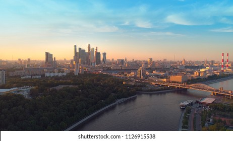 Moscow International Business Center, Moscow-city. A sunset aerial shot of skyscrapers with beautiful evening sky and the Moscow river on the background. Aerial high altitude drone flight.