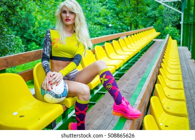 MOSCOW - JUL 16, 2015: beautiful woman (with model release) with ball in his hands in yellow top resting on bench