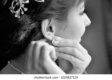 MOSCOW – JULY 13, 2013: Morning gathering of the bride. Bride puts on an earrings. Black and white.