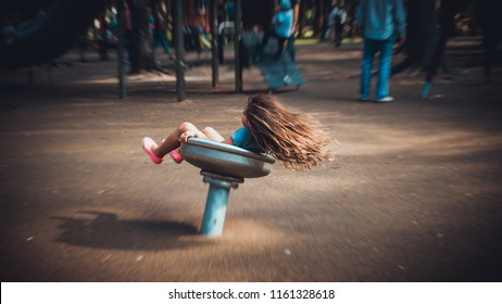 MOSCOW - JULY 18, 2018: In the summer park, on the playground, the girl is spinning on the carousel.