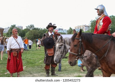 Moscow - July 7, 2012: Cossack and musketeer looks at the passing knights on horseback at the Historical festival Times and Epochs. Public-event.