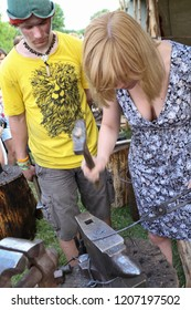 Moscow - July 7, 2012: Experienced blacksmith teaches the craft of a girl at the Historical festival Times and Epochs. Public-event.