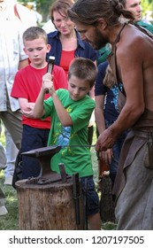 Moscow - July 7, 2012: Experienced blacksmith teaches the craft of a young man at the Historical festival Times and Epochs. Public-event.