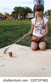 Moscow - July 7, 2012: Girl playing 'gasing' or top spinning, a russian traditional old game at the Historical festival Times and Epochs. Public-event.