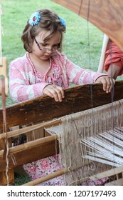 Moscow - July 7, 2012: Girl make cloth on the loom at the Historical festival Times and Epochs. Public-event.
