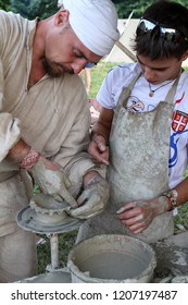 Moscow - July 7, 2012: Potter teaches man skills at the Historical festival Times and Epochs. Public-event.