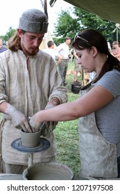 Moscow - July 7, 2012: Potter teaches girl skills at the Historical festival Times and Epochs. Public-event.