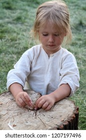 Moscow - July 7, 2012: Young beautiful girl playing on the stump at the Historical festival Times and Epochs. Public-event.