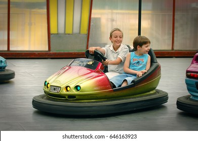 MOSCOW, JULY 9, 2005: Smiling children drive small electric car in Sokolniki Entertainment park. Two kids children have fun on famous classic attraction amusement small electric automobiles. Pure joy