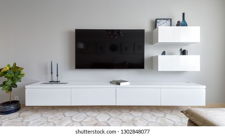 Moscow - June 18, 2018: Modern home interior with TV and flower. Light interior design of living room. Panoramic view of the stylish minimalist white interior of flat in daylight.