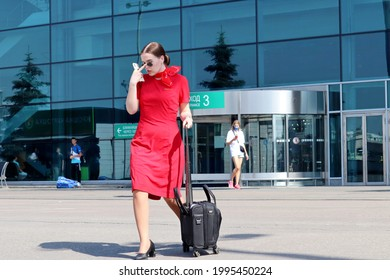 Moscow, Russia - June 2021: Young woman in red stewardess uniform walking with luggage in Domodedovo airport terminal