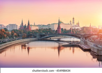 Moscow Kremlin with reflection in the river in a pink-gold haze