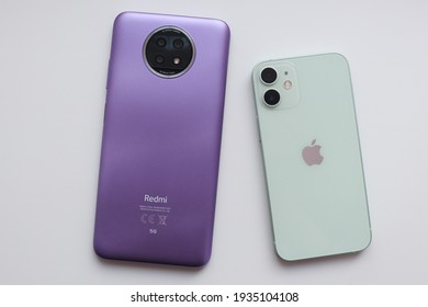 MOSCOW - MAR 13, 2021: photographer is showing a brand new Xiaomi Redmi Note 9T 5G and comparing it with Apple iPhone 12 mini