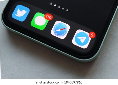 MOSCOW - MAR 20, 2021: iPhone 12 mini with Telegram, Safari, iMessage and Twitter app icons on screen