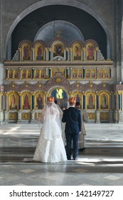 MOSCOW - MARCH 10: crowned bride and groom stand in the church behind the priests during orthodox wedding ceremony on March 10, 2013 in Moscow