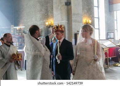 MOSCOW - MARCH 10: priest crowns groom during orthodox wedding ceremony on March 10, 2013 in Moscow