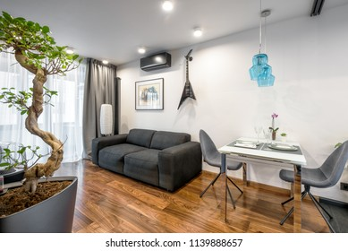 Moscow - March 25, 2018: Modern home interior with couch, table and plants. Beautiful minimalist interior design of living room with white walls. Luxury natural wooden floor in apartment interior.