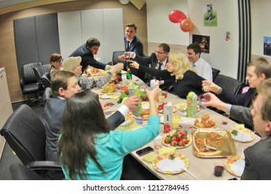Moscow March 8, 2017: Happy staff at cafe table in business office celebrating success or starting new project. Men congratulate women in office on Women's Day.