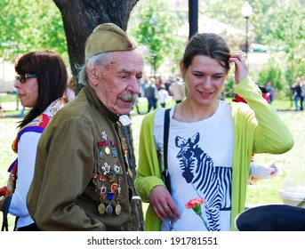 MOSCOW - MAY 09, 2014: Portrait of a war veteran and young woman. Victory Day celebration in Moscow.