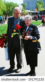 MOSCOW - MAY 09, 2014: A woman war veteran walks with flowers in Gorky park. Victory Day celebration in Moscow.