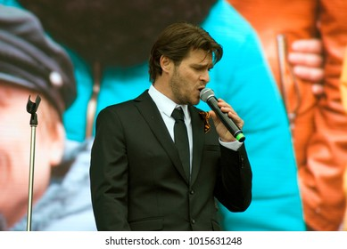 MOSCOW - MAY 09, 2017: Singer Julien Dassin performs on stage in Gorly park. Free entrance public event. War veteran portrait. Victory Day celebration in Moscow. Color photo.