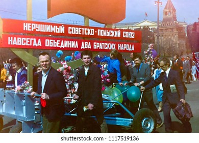 MOSCOW - MAY 1, 1987: Soviet people with banners on trolley move in demonstration devoted to First of May Holiday against Kremlin background on May 1, 1987 in Moscow.