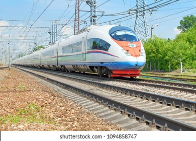 MOSCOW, MAY, 18, 2018: Diagonal view on high speed train runs on rail way tracks and trees in the background. Russian railways electric high speed passenger commuter Sapsan train. Intercity express