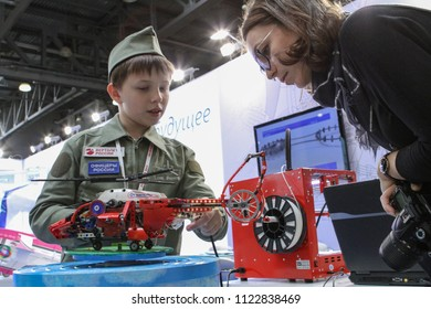 Moscow - May 26, 2018: Kid and woman with RC helicopter, focus on the helicopter at the international exhibition of  the helicopter industry, HeliRussia. Public-event.