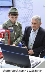 Moscow - May 26, 2018: A man and a child are studying a program for working on a 3D printer at the international exhibition of  the helicopter industry, HeliRussia. Public-event.