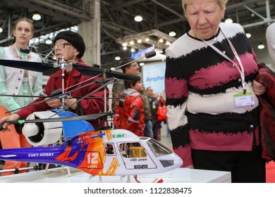 Moscow - May 26, 2018: Old woman and RC helicopter, focus on the helicopter at the international exhibition of  the helicopter industry, HeliRussia. Public-event.