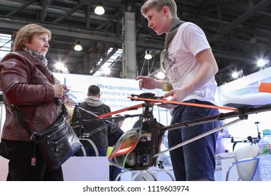 Moscow - May 26, 2018: Woman, kid and helicopter at the international exhibition of  the helicopter industry, HeliRussia. Public-event.