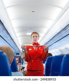 MOSCOW - MAY 28, 2011: Air hostess Yulia of Aeroflot shows how to use a safety belt on board. Aeroflot operates the youngest fleet in the world among major airlines, numbering 150 airliners.