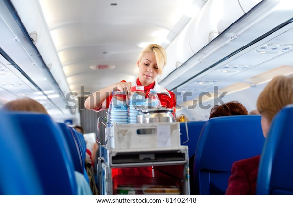 "MOSCOW - MAY 28: Unidentified air hostess of ""Aeroflot"" serves drinks out on board from Irkutsk to Moscow, May 28, 2011. ""Aeroflot"", the national carrier, leads in growth rate in 2011, Moscow, Russia."