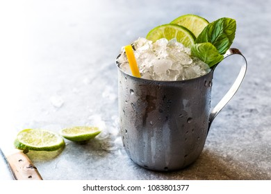 Moscow Mule Cocktail with Lime, Mint Leaves and Crushed Ice in Metal Cup / Mint Julep