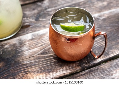 A Moscow Mule in a copper mug on an old wooden table on a summer day.