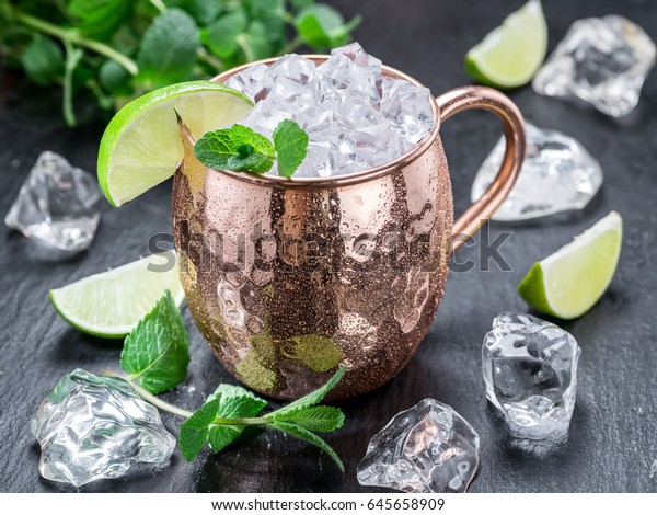 Moscow Mule. Frosty copper mug with lime and ice cubes on the  table.