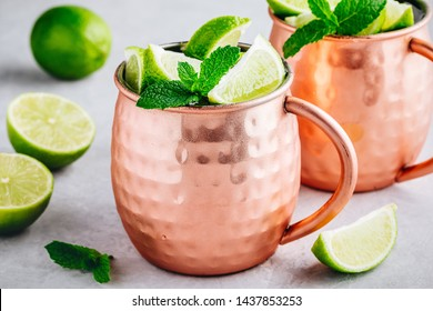 Moscow mule ice cold cocktail in copper cup with lime and and mint on gray stone background, copy space.