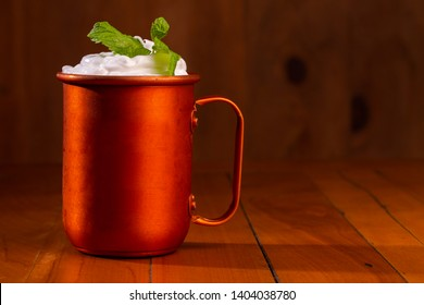 Moscow mules cocktail in copper mugs with green mint leaves. Beautiful and delicius Moscow Mule drinks served on a wooden table